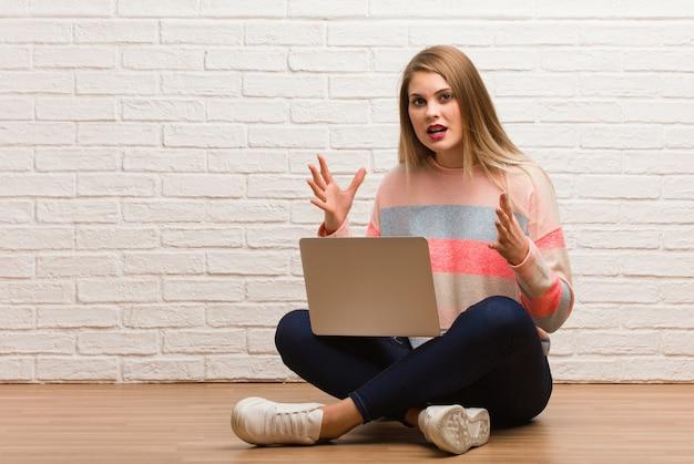 勝利または成功を祝って座っている若いロシア学生女性 Premium写真