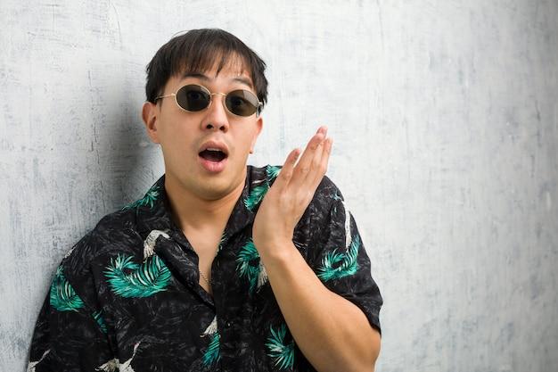 驚きとショックを受けた夏服を着ている若い中国人男性 Premium写真