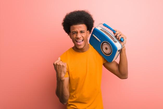 ビンテージのラジオを保持している若いアフリカ系アメリカ人の驚きとショックを受けた Premium写真