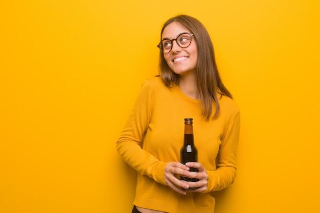 Молодая милая кавказская женщина усмехаясь уверенно и скрещивая оружия, смотря вверх. она держит пиво. Premium Фотографии