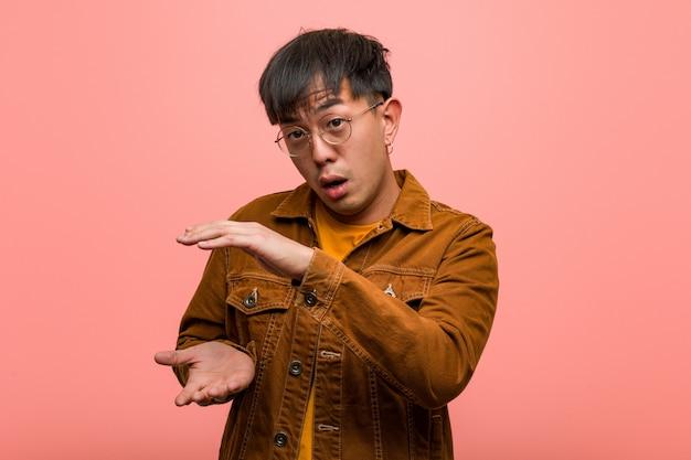 非常に驚いてショックを受けて何かを保持しているジャケットを着ている若い中国人男性 Premium写真