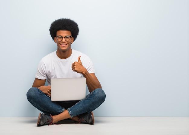笑みを浮かべて、親指を上げるノートパソコンで床に座っている若い黒人男性 Premium写真