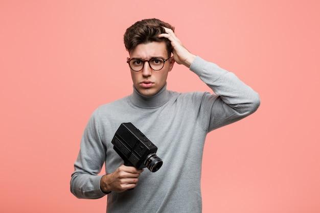 ショックを受けているフィルムカメラを持っている若い知的男、彼女は重要な会議を覚えています。 Premium写真