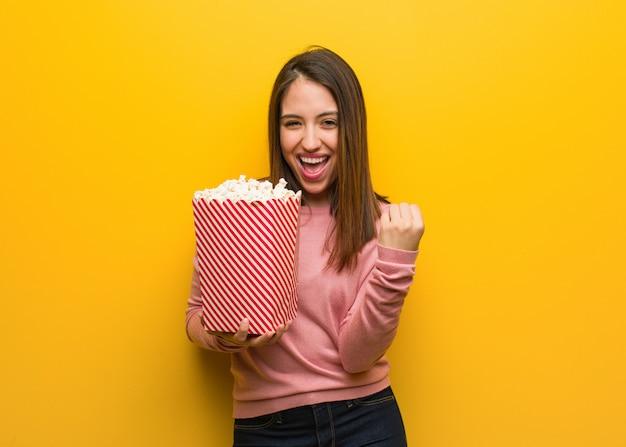 Молодая милая женщина, держащая ведро попкорна удивлен и шокирован Premium Фотографии