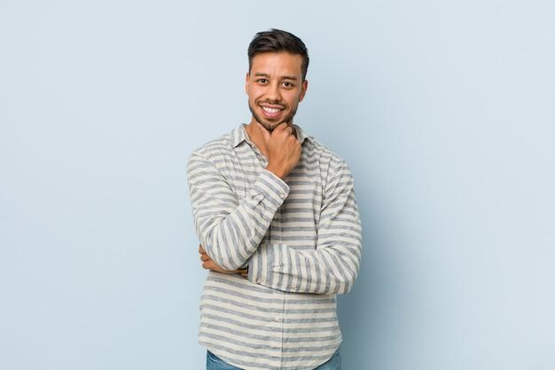 幸せで自信を持って、あごに手を触れて笑顔若いハンサムなフィリピン人男性。 Premium写真