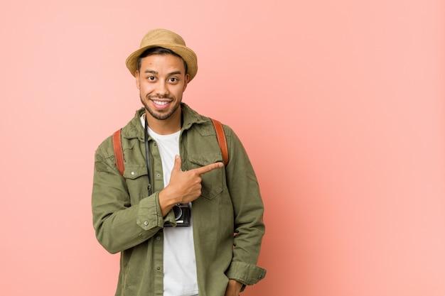 Молодой филиппинский путешественник человек улыбается и указывая в сторону, показывая что-то на пустое пространство. Premium Фотографии