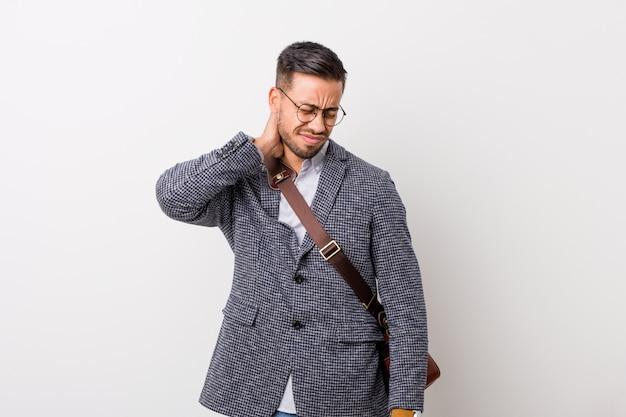 座りがちなライフスタイルによる首の痛みに苦しんでいる白い壁に対して若いビジネスフィリピン人男性。 Premium写真