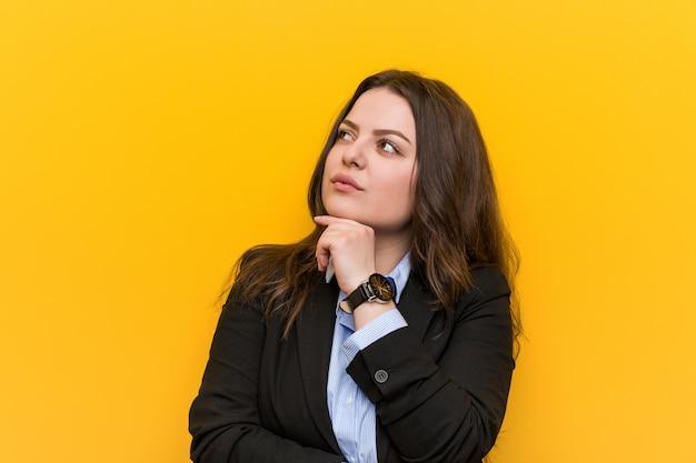 疑わしいと懐疑的な表情で横に探している若いプラスサイズの白人女性。 Premium写真