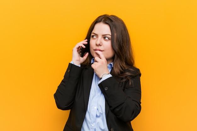 疑わしいと懐疑的な表現で横に探している携帯電話を保持している若い曲線プラスサイズビジネス女性。 Premium写真