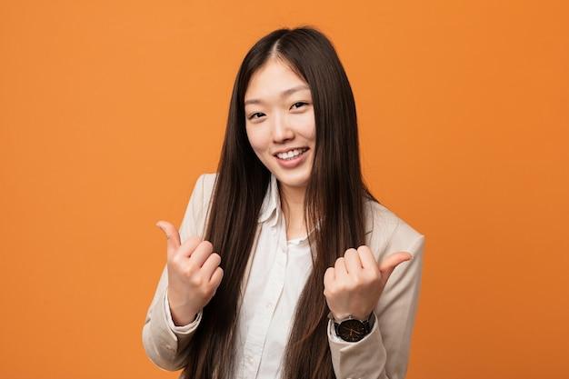 若いビジネス中国の女性両手を上げて、笑って自信を持っています。 Premium写真