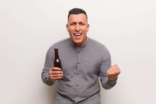 Молодой человек латинской держит пиво удивлен и шокирован Premium Фотографии