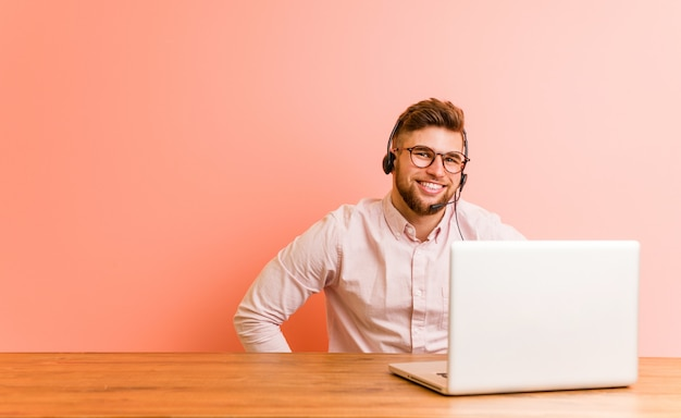 Молодой человек, работающий в колл-центр, уверенно держа руки на его бедра. Premium Фотографии