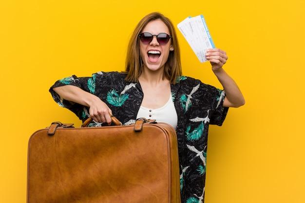Молодая женщина готова пойти в отпуск на желтом фоне Premium Фотографии