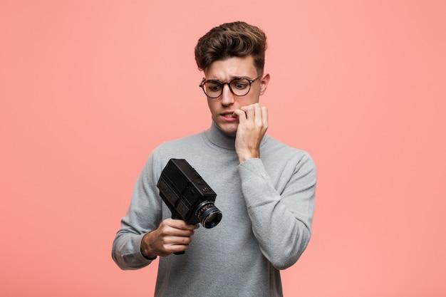 爪をかむ、緊張し、非常に心配しているフィルムカメラを保持している知的な若者。 Premium写真