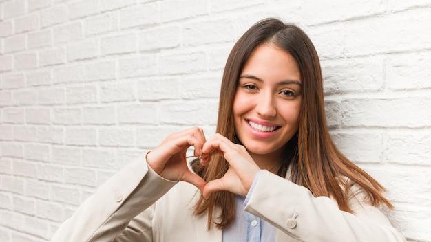 手でハートをやっている若いビジネス女性 Premium写真