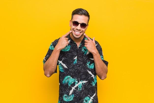 夏服を着て笑顔のフィリピン人男性、口に指を指しています。 Premium写真