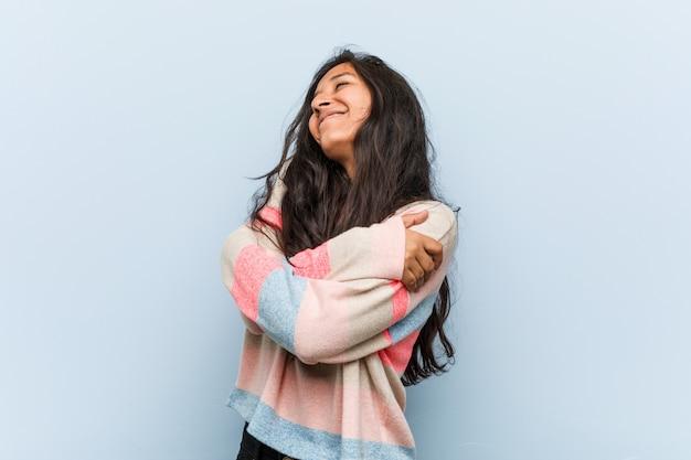Молодая модная индийская женщина обнимает себя, улыбается беззаботной и счастливой. Premium Фотографии