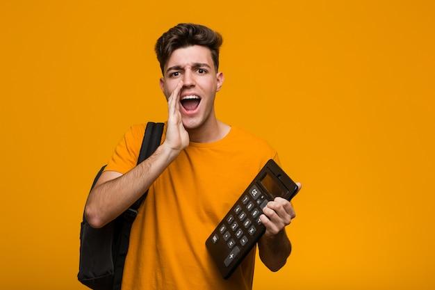 先に人差し指で陽気に指している笑みを浮かべて電卓を持って若い学生男。 Premium写真