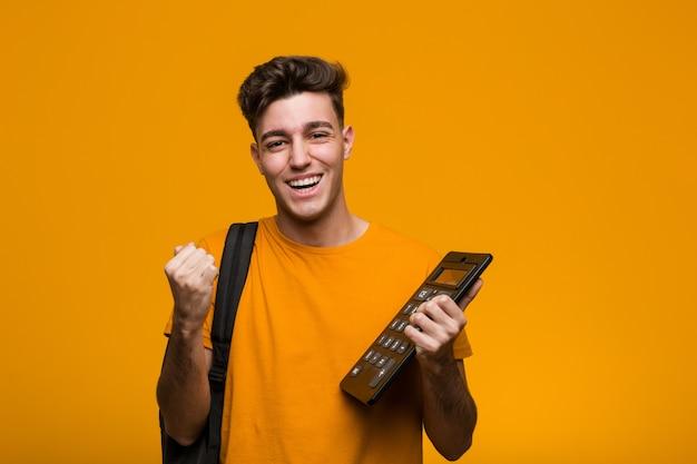 勝利または成功を祝う電卓を持って若い学生男 Premium写真