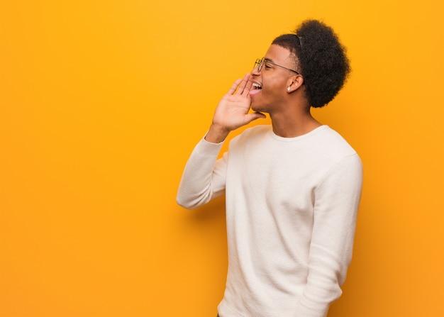 Молодой афроамериканец человек над оранжевой стеной шепотом сплетни подтекст Premium Фотографии