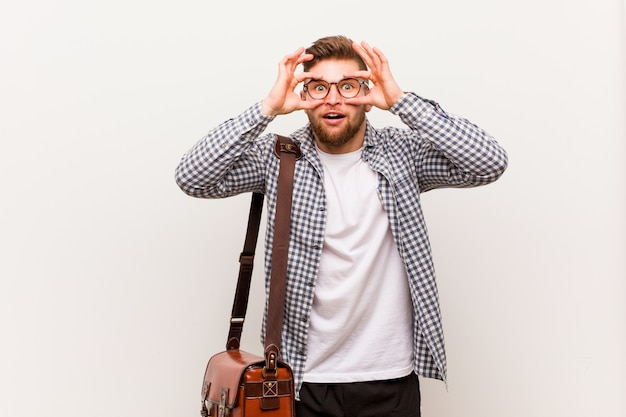 Молодой современный деловой человек держать глаза открытыми, чтобы найти возможность успеха. Premium Фотографии