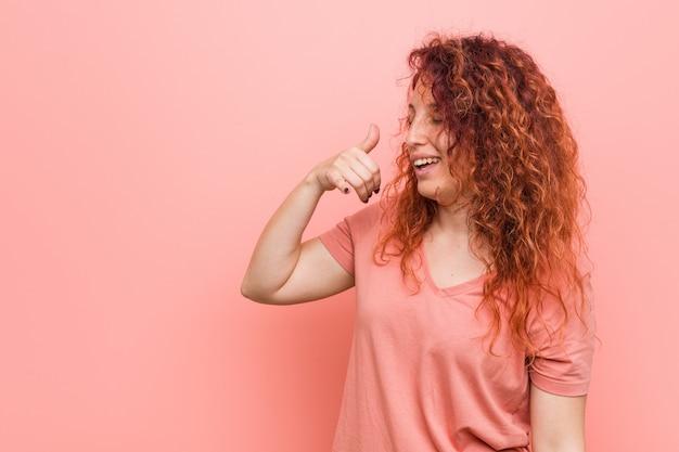 携帯電話を示す自然で本格的な赤毛の女性が指でジェスチャーを呼び出します。 Premium写真