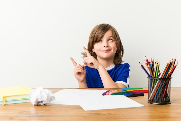 絵を描いて、彼の机の上に宿題をしている少年はショックを受けました。 Premium写真