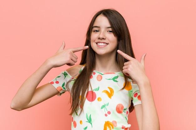 赤い壁に夏の服を着ている少女の笑顔、口に指を指しています。 Premium写真