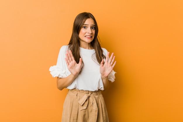 Молодая кавказская женщина отвергая кто-то показывая жест отвращения. Premium Фотографии