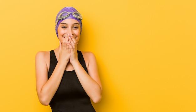 若いスイマー白人女性何かについて笑って、手で口を覆っています。 Premium写真