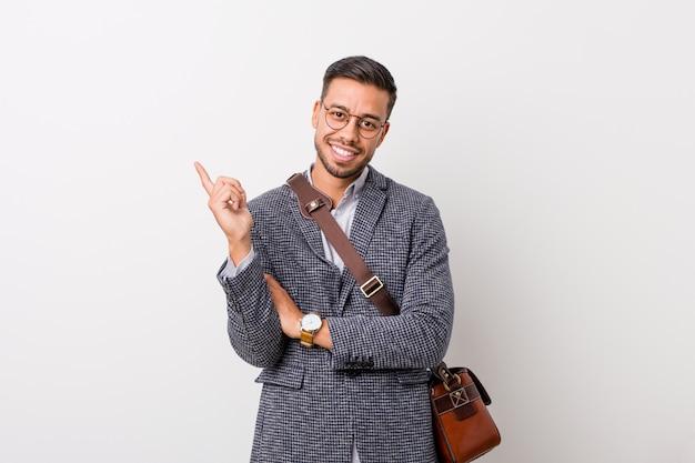 人差し指で元気に指している笑みを浮かべて白い壁に若いビジネスフィリピン人。 Premium写真