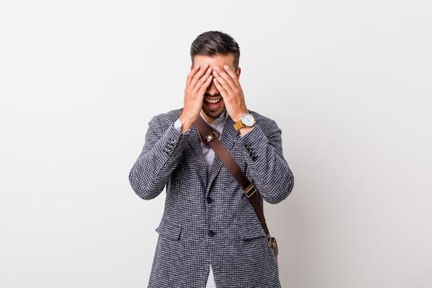 Молодой деловой филиппинский мужчина у белой стены закрывает глаза руками, широко улыбаясь в ожидании сюрприза. Premium Фотографии