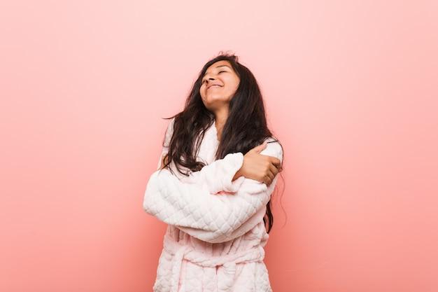 パジャマを身に着けている若いインド人女性は、屈託のない幸せな笑みを浮かべて自分を抱擁します。 Premium写真