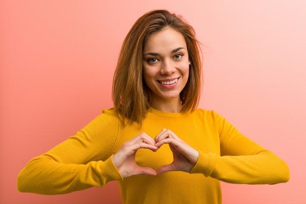 笑顔と彼女の手でハートの形を示す若いかなり若い女性。 Premium写真