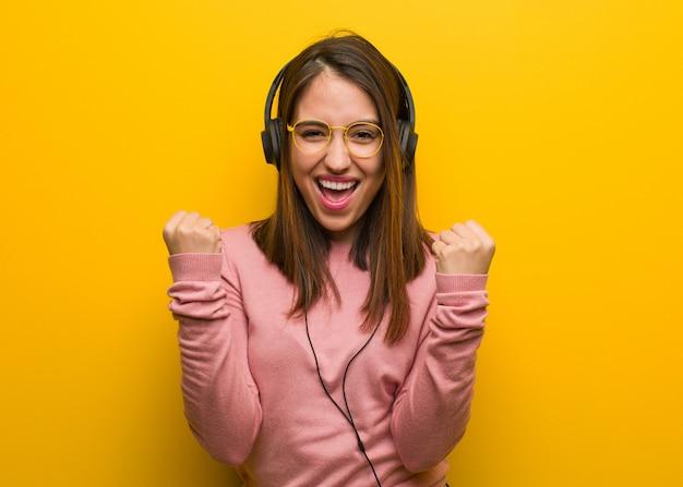 Молодая милая женщина слушает музыку удивлен и шокирован Premium Фотографии