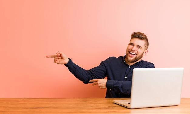 Молодой человек, работающий с его ноутбуком возбужденных, указывая указательными пальцами прочь. Premium Фотографии