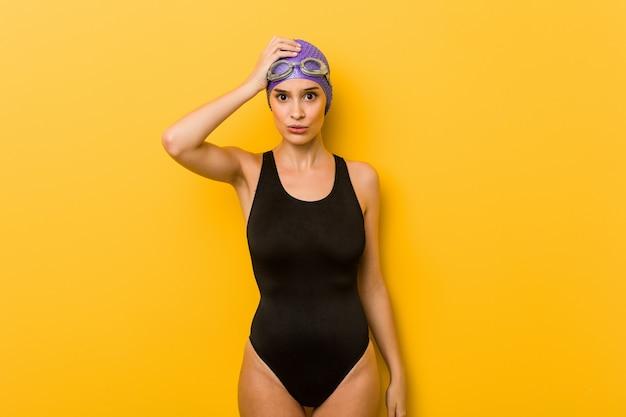 若いスイマーの白人女性は疲れて非常に眠い頭に手をつないでいます。 Premium写真