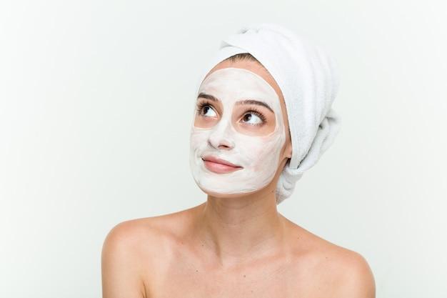 顔面マスク治療を楽しんでいる若い白人女性 Premium写真