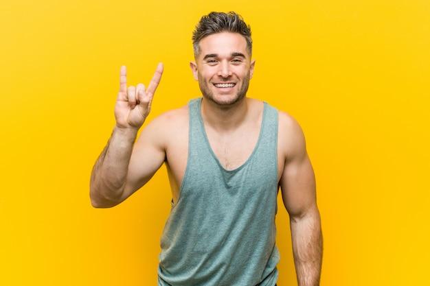 革命として角ジェスチャーを示す黄色に対する若いフィットネス男。 Premium写真