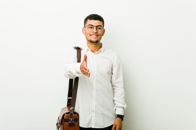 ジェスチャーの挨拶で手を伸ばす若いヒスパニックカジュアルビジネス男。 Premium写真