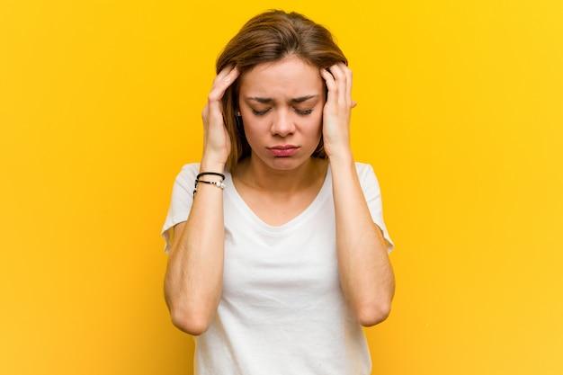 Молодая естественная кавказская женщина касаясь его вискам и имея головную боль. Premium Фотографии
