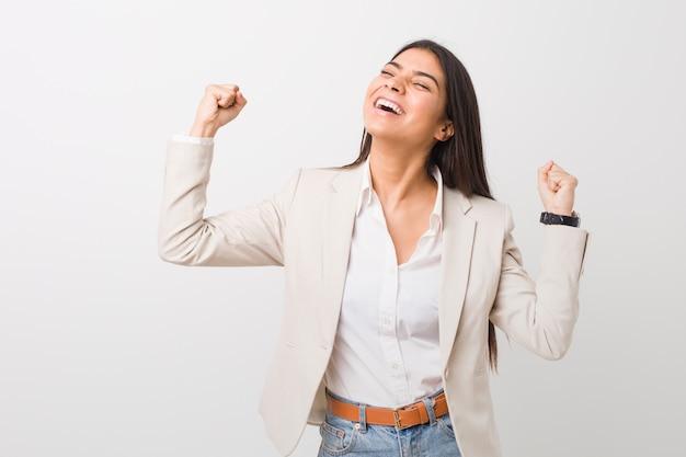 Женщина молодого дела арабская изолированная против белого поднимая кулак после победы, победителя. Premium Фотографии