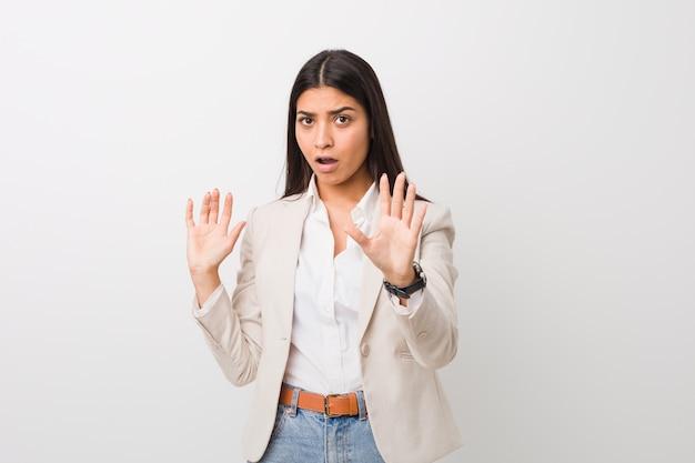 デュエアン差し迫った危険にショックを受けている白に対して分離された若いビジネスアラブ女性 Premium写真