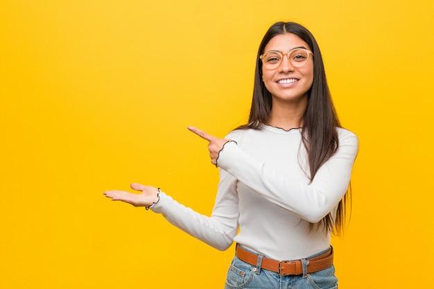 黄色に対してかなり若いアラブ女性興奮して手のひらを保持しています。 Premium写真