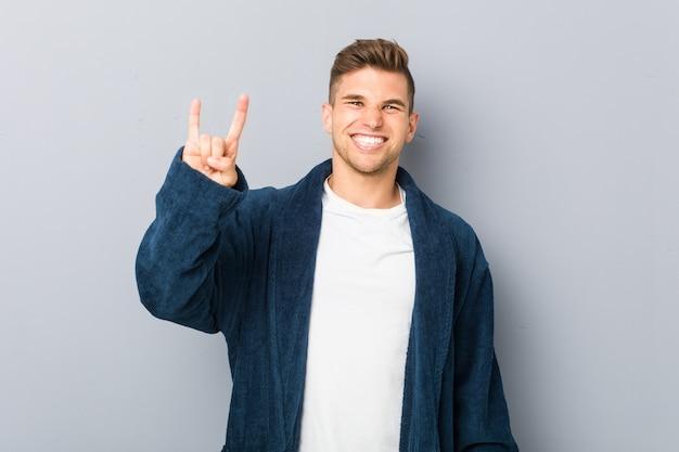 革命の概念として角のジェスチャーを示すパジャマを着ている若い白人男。 Premium写真