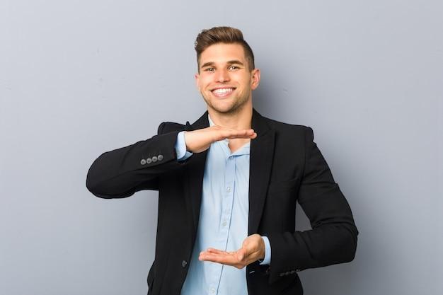 製品プレゼンテーション、両手で何かを保持している若いハンサムな白人男性。 Premium写真