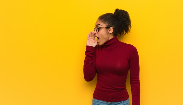 Молодая черная афроамериканская девушка с голубыми глазами шепчет сплетни подтекст Premium Фотографии