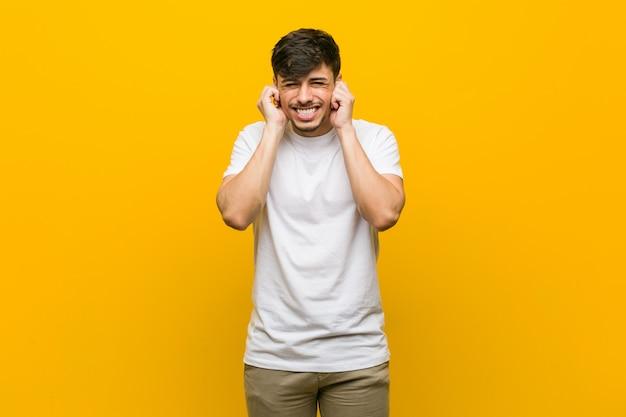 若いヒスパニック系のカジュアルな男の手で耳を覆っています。 Premium写真