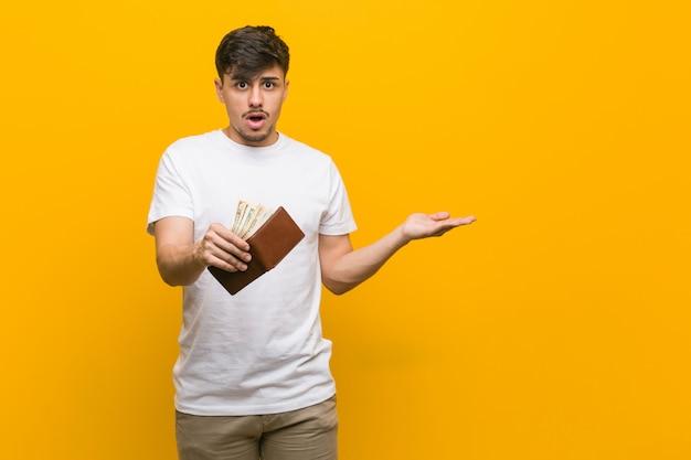 財布を保持しているヒスパニック青年は、手のひらにコピースペースを保持していることに感銘を受けました。 Premium写真