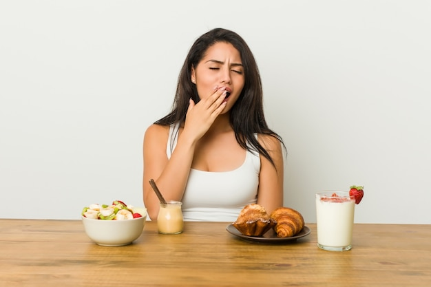 Молодая соблазнительная женщина, принимая завтрак зевая, показывая усталый жест, охватывающий рот рукой. Premium Фотографии